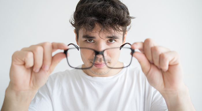Homem branco, usando uma camiseta branca, na frente de um fundo claro, com um par de óculos posicionado em frente ao seu rosto, como se fosse coloca-los.